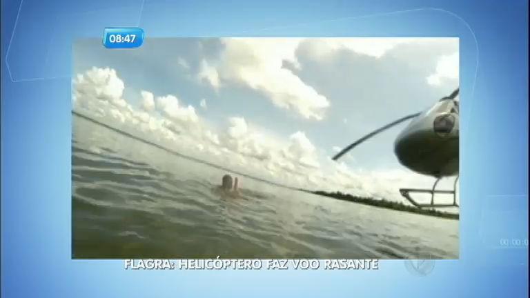 Helicóptero faz voo rasante perto de banhistas em rio na divisa ...