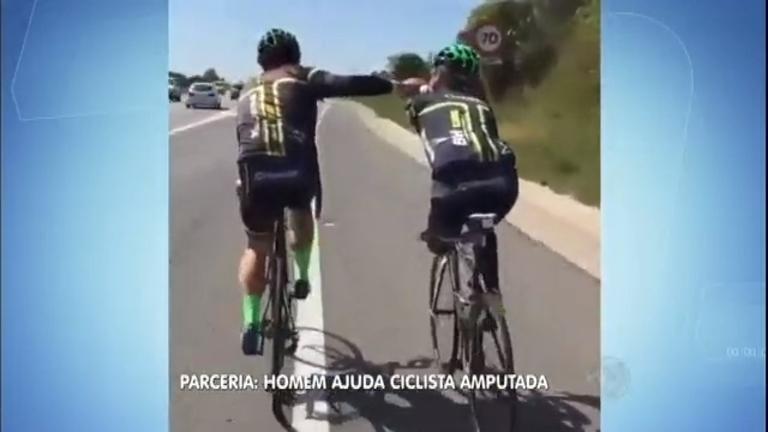 Ciclista sem braço e perna recebe ajuda de outro homem de bicicleta