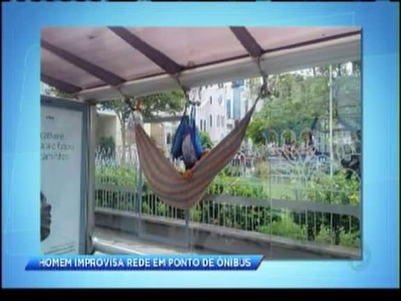 Homem improvisa rede em ponto de ônibus